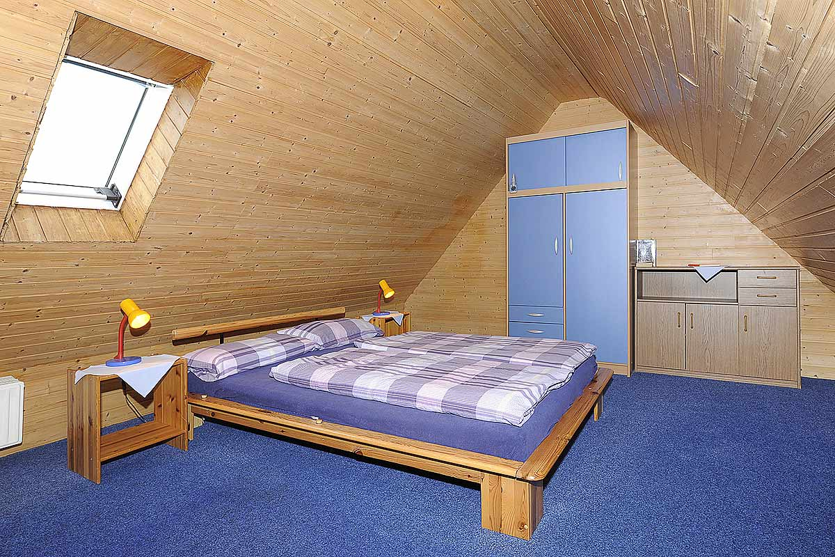 Schlafzimmer mit Doppelbett und Schränken im Dachgeschoß der Ferienwohnung